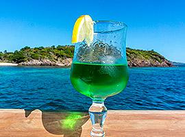 Genieße Cocktail auf deiner Yacht mit Ausblick auf grüne Inseln | sailwithus