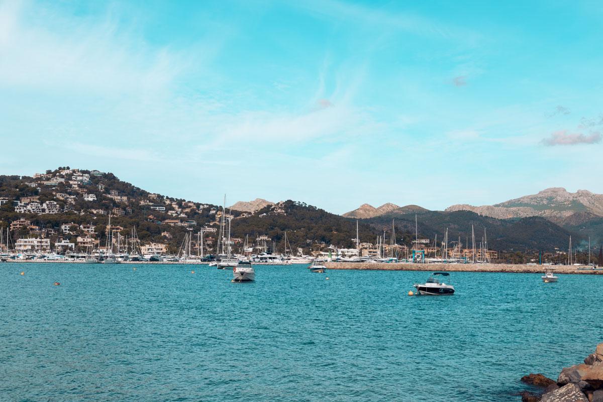 Yachten und Segelbooten in der Marina von Mallorca, schöne Stadt mit vielen Böumen, Natur und Berge im Hintergrund
