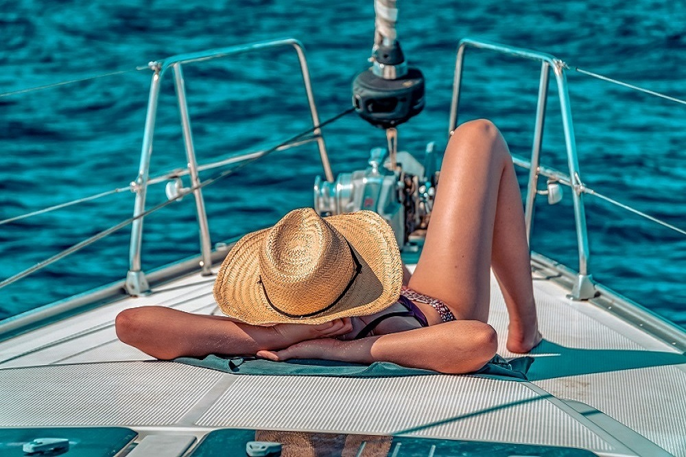 Sonnenbaden mit Sonnenhut an Board auf dem Sonnendeck der Segelyacht