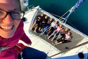 Crewmitglied hängt am Mast und dokumentiert den Rest der Crew beim Entspannen von dem aufgrenden Segeltag