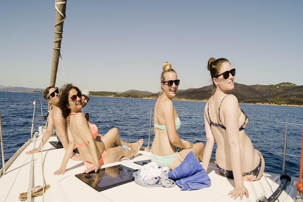 Die Segel Crew entspannt an Deck in der Sonne und hat viel Spaß dabei, kein Wunder bei dieser tollen Aussicht auf das Festland Frankreichs