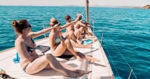 Crew entspannt an Deck der Yacht in einer einsamen Bucht in der Sonne