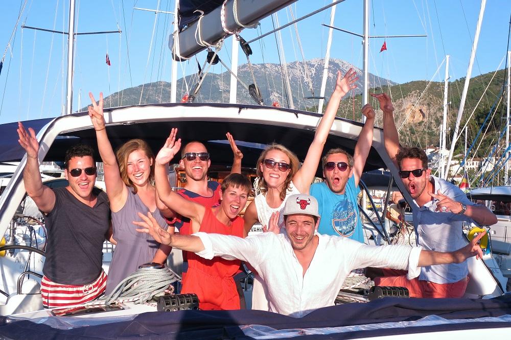 Gruppenfoto der gut gelaunten Crew in einem Hafen in Griechenland