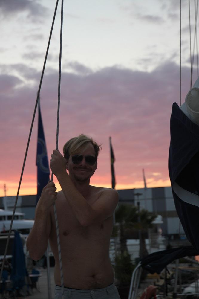 Crewmitglied hält sich an einer Leine an Bord fest und genießt die Abendstimmung mit tollem Abendrot