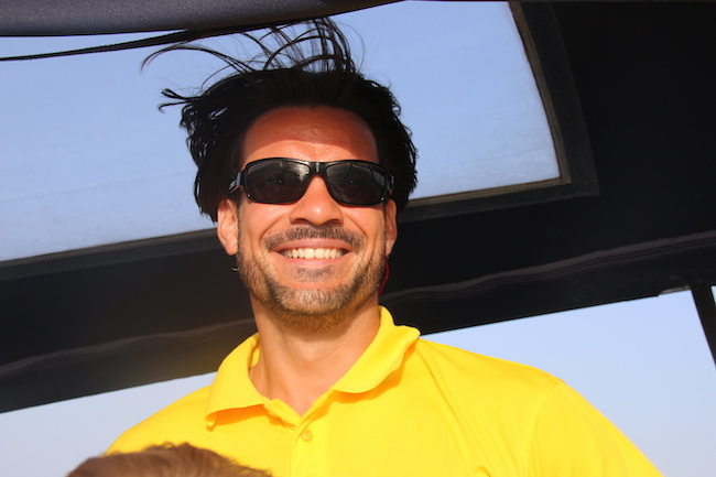 Skipper Konrad im gelben sailwithus Poloshirt mit Sonnenbrille und breitem Lächeln