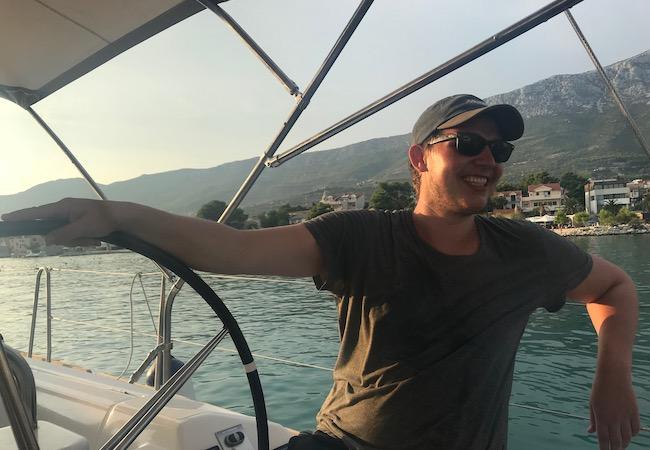 Matthias, ein Skipper von Sailwithus am Steuer mit Sonnebrille, Capy und guter Laune