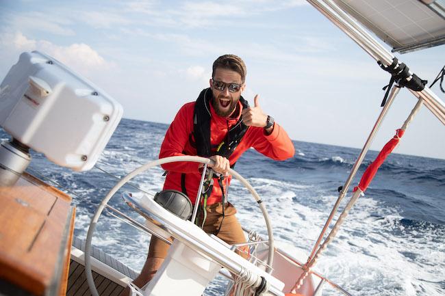 Skipper Max von Sailwithus mit roter Jacke und Sonnebrielle an Bord der modernen Segelyacht mit guter Laune auf rauher See