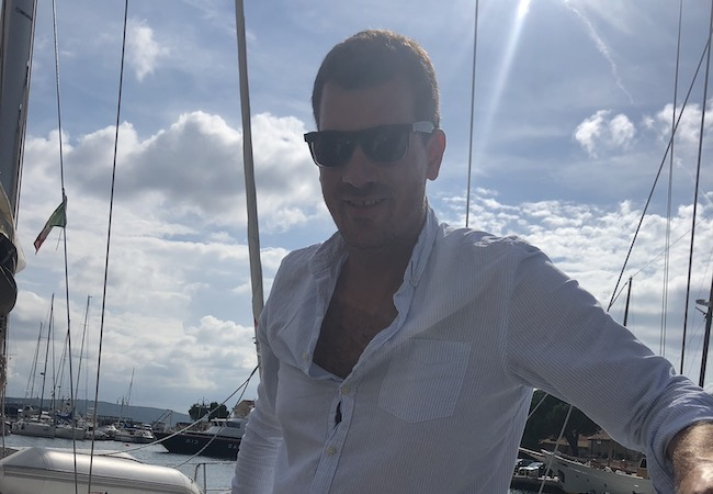 Skipper Stefan mit Sonnenbrille an Deck im Mittelmeer in der Sonne