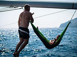 Pärchen an Bord der modernen Yacht im Mittelmeer wirft sich Küsse zu