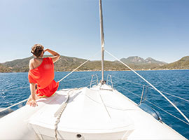 Mitseglerin im roten Kleid entspannt auf dem Bug der Yacht im Mittelmeer