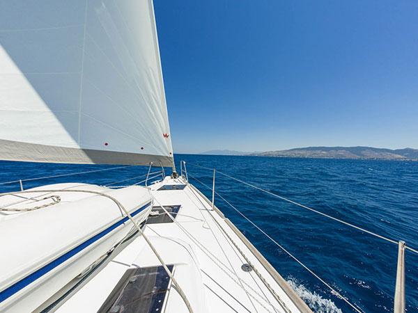 Eine weiße Yacht zischt durch das blaue Wasser des Mittelmeers mit dem Festland im Hintergrund
