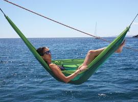Mama entspannt mit einem Sundowner in der HÄngematte an Bord der Segelyacht