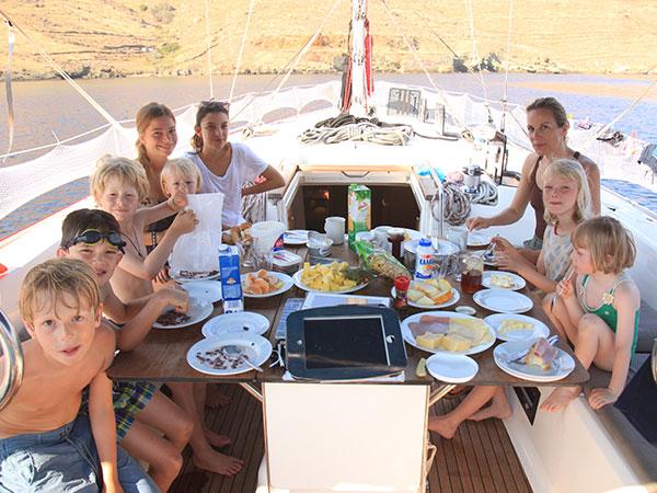Die jungen Familien genießen das Mittagessen an Bord der modernen Yacht vor der Küste Griechenlands