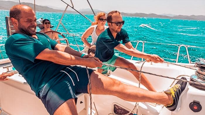 Crew arbeitet zusammen am Segel setzen, Spaß am Segeln
