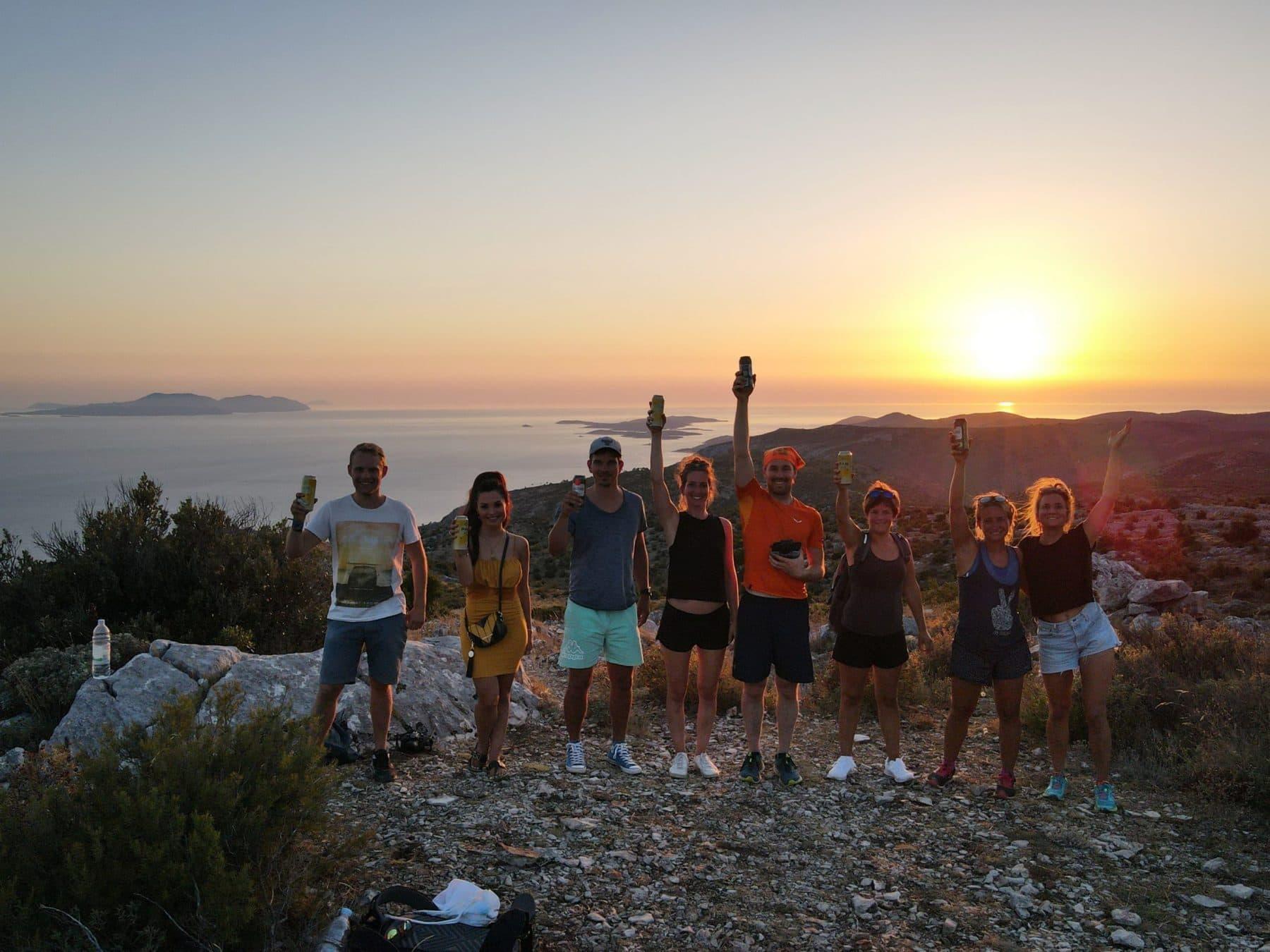 junge Crew auf ihrem Landausflug bestaunen den Sonnenuntergang im Urlaub mit sailwithus