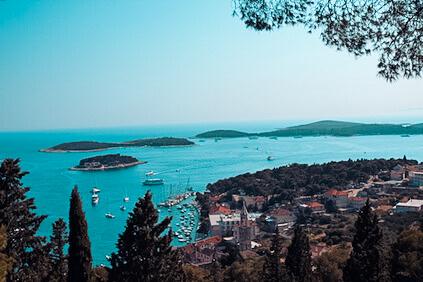 Weiter Ausblick über Hafenstadt und grüne Inseln