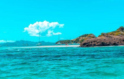 Kleine Bucht mit weißem Sand, braunen Felsen endecken auf der Segelreise in der Karibik