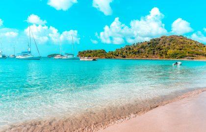 Fünf Yachen ankern vor karibischen Inseln und fahren mit dem Dinghy an Land