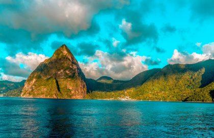 Toller grüner Felsen und grüne Hügel überragen traumhaftes Wasser mit vielen Yachten in der Karibik