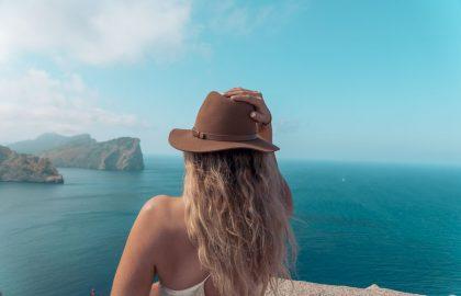 Blonde Frau mit braunem Haut begutachet den endlosen Horiziont mit Felsen die in das blaue Meer ragen