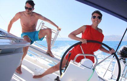 Mitseglerin im roten Kleid am Steuer fährt durch das Mittelmeer Griechenlands