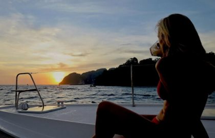 Crewmitglieder genießen den Sonnenuntergang in Thailand auf der Segelyacht mit einem Sundowner