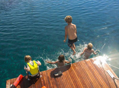 Die Kids genießen die Badeplattform, springen und schwimmem im Wasser