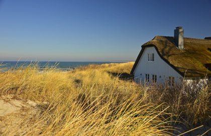 Weißes Haus mit Strohdach auf den Dünen direkt am Meer mit Blick auf die Ostsee Segler