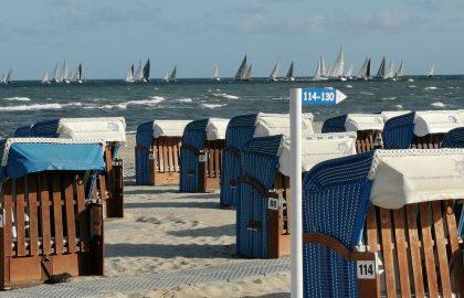 Strandkörbe am Ostsee Strand mit Blick auf Segler und kleine Wellen